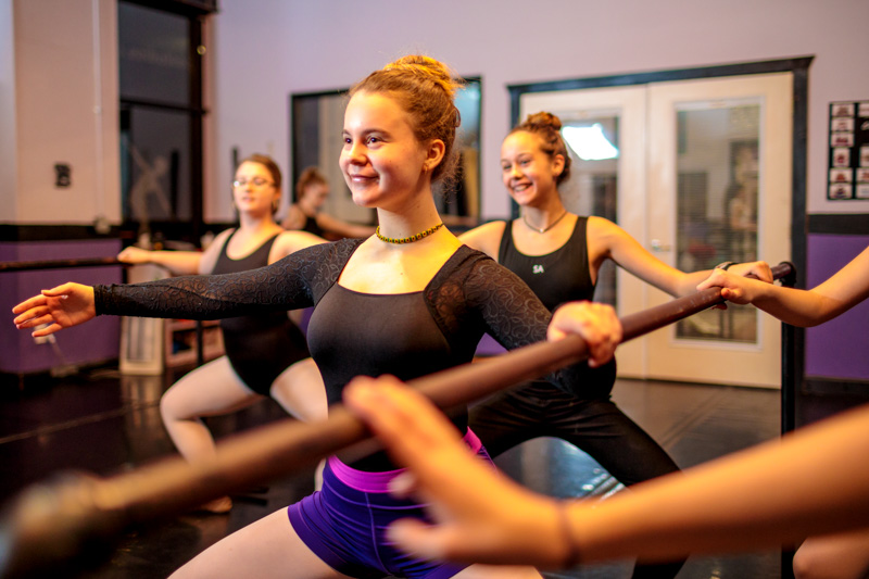 Happy ballerina performing a plie' in dance class.